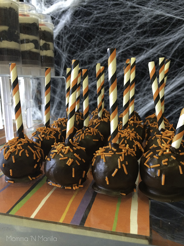 Cake Pops were made with our Cake Pop Maker. We used a vanilla recipe to make the balls, trimmed the excess and then dipped in Tulip Chocolate Compound that we got from our local bake shop supply as well as our Halloween themed paper straws that we used in place of sticks.